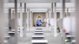 Zdravotníčka NHS sa pozerá pri vakcinačných paneloch počas príprav na očkovanie vakcínou proti ochoreniu COVID-19 od spoločnosti AstraZeneca/Oxford v masovom vakcinačnom centre Elland Road v anglickom meste Leeds 9. februára 2021.