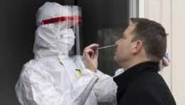 Na snímke zdravotník odoberá vzorku z nosa počas testovania na ochorenie COVID-19.