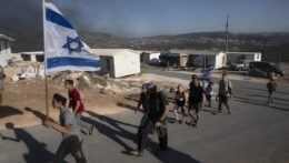 Izraelskí osadníci nesú vlajku na základni Eviatar neďaleko mesta Nábul na Západnom brehu.