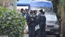 Príslušníci polície zhromaždení okolo policajného auta v Nemeckom Hanau.