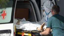zdravotníci nakladajú pacienta do sanitky