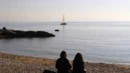 Na snímke ľudia sedia pri mori v Chorvátsku.
