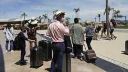 Turisti s batožinou čakajúci na odlet.