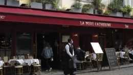 Čašník stojí pred reštauráciou na letnej terase po jej znovuotvorení po lockdowne v štvrti Montmartre v Paríži 19. mája 2021.