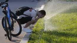 Muž sa osviežuje vodou určenou na zavlažovanie trávnika.