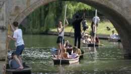 Ľudia sa plavia na člne na rieke Cam v anglickom meste Cambridge počas horúceho dňa v stredu 16. júna 2021.