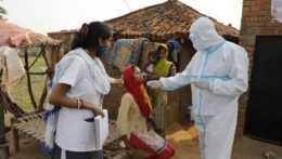 Zdravotníci odoberajú žene vzorku na vykonanie testu na prítomnosť koronavírusu v dedine na indickom vidieku.