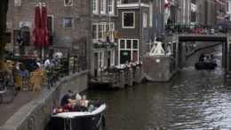 Ľudia na terasách podnikov v Amsterdame.