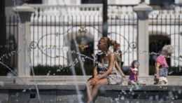 Žena sedí na fontáne.