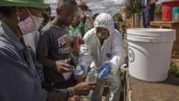 Pracovník v ochrannom odeve pomáha ľuďom na Madagaskare.