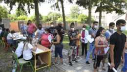 ľudia stoja v rade na očkovanie