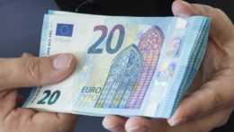 Človek drží v rukách dvadsaťeurové bankovky.