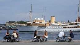 Ľudia na letnej terase kaviarne v prístave v Kodani.