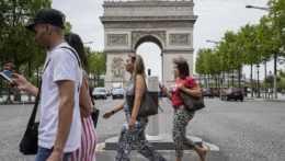 Ľudia kráčajú okolo Víťazného oblúka na Elyzejských poliach v Paríži.