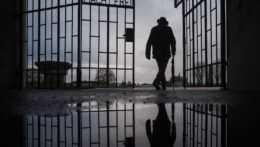 Muž kráča cez bránu v bývalom koncentračnom tábore Sachsenhausen.