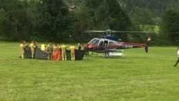 Záchranári vedľa polcajného vrtuľníka v rakúskych Alpách.