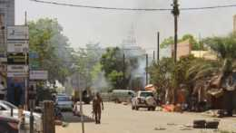 ozbrojení muž kráčajúci ulicou v Burkine Faso