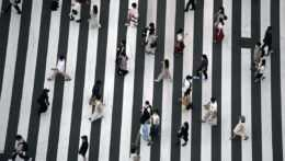 Ľudia s rúškami na priechode pre chodcov.