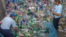 Pracovníci triedia PET fľaše pri lise triedeného odpadu.
