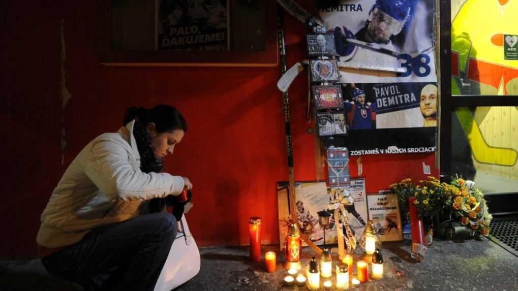 fanúšička zapaľuje sviečku na pamiatku Pavla Demitru