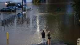 Ľudia sa pozerajú na zaplavenú ulicu vo Philadelphii.