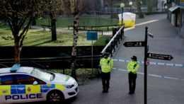 policajti hliadkujúci pred miestom činu
