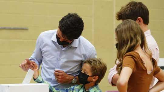 kanadský premiér Justin Trudeau v spoločnosti svojich detí vhadzuje do urny volebný lístok