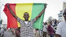 muž drží nad hlavou malijskú vlajku