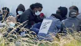 Migranti sedia na pláži.