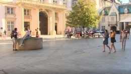 Ľudia sa prechádzajú na námestí v Bratislave.