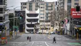 Ľudia prechádzajú cez takmer prázdne ulice v novozélandskom meste Auckland