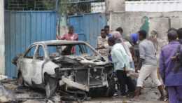 Ľudia sa zhromaždili pri vraku auta po bombovom útoku