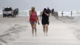 Ľudia si zakrývajú tváre počas búrky Nicholas v Texase.