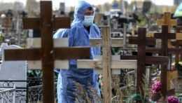 Hrobár v ochrannom odeve stojí počas pohrebu obete koronavírusu na cintoríne v Omsku