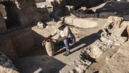 Archeológ drží starý džbán na víno.