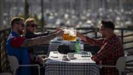 ľudia si pripíjajú na terase reštaurácie