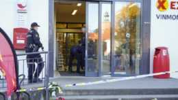 Policajti pred obchodom v nórskom meste Kongsberg po útoku muža s lukom a šípmi.