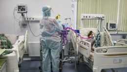 zdravotník v ochrannom obleku ošetrujúci pacienta s covidom v nemocnici v Nižnom Novgorode